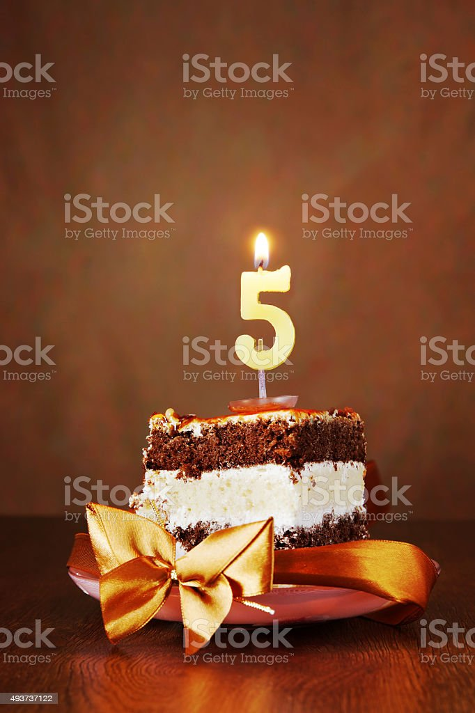 Piece of Birthday Cake with Burning Candle as Number Five stock photo