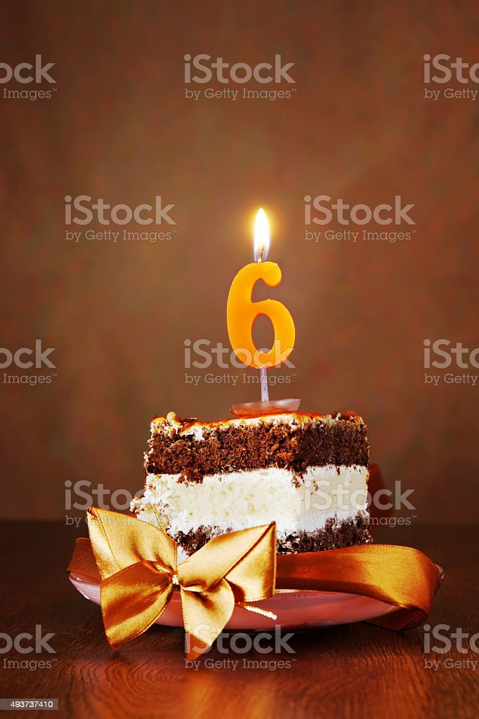 Piece of Birthday Cake with Burning Candle as Number Six stock photo