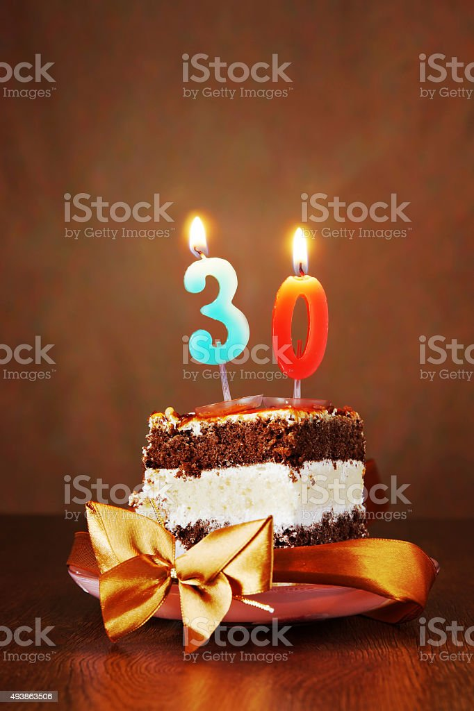 Piece of Birthday Cake with Burning Candle as Number Thirty stock photo