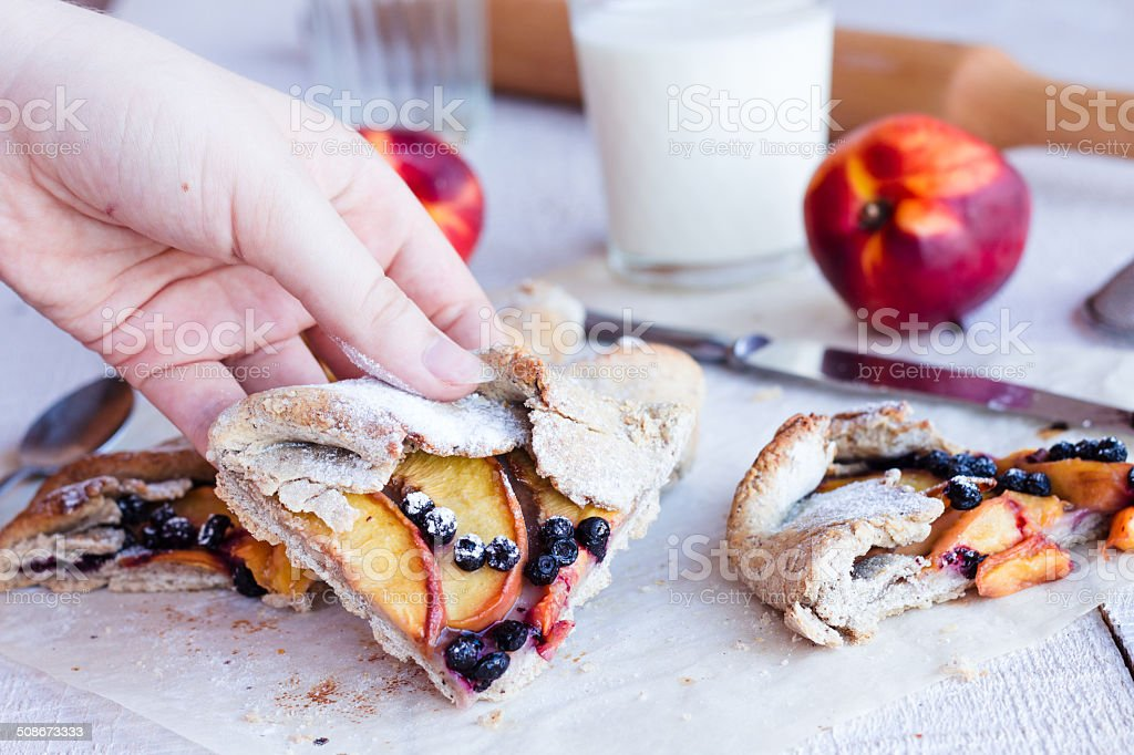 piece of biscuit with peach and blueberry in hand stock photo