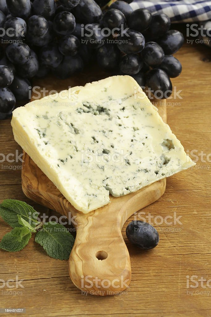 piece of blue cheese with grapes on a wooden board stock photo