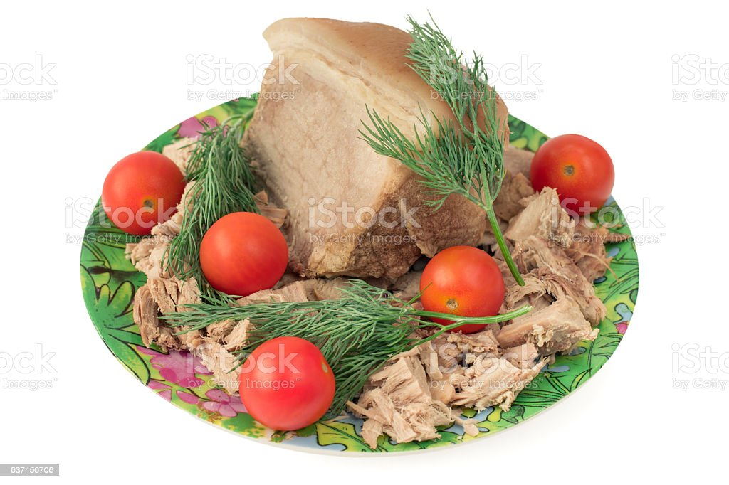 Piece of boiled pork on a plate with cherry tomatoes. stock photo
