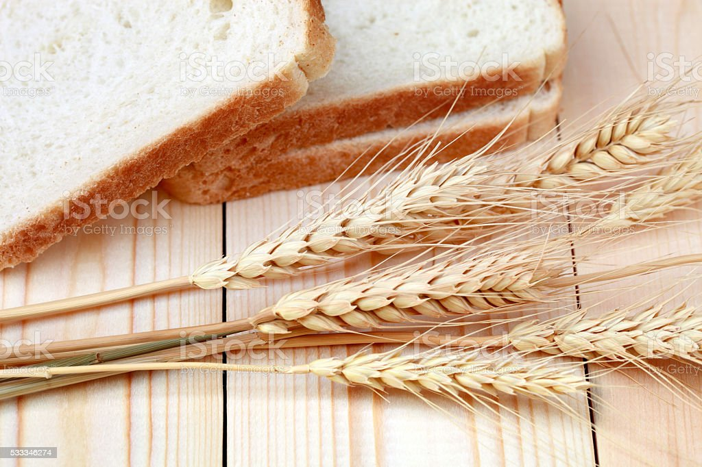 Piece of bread and wheat ears stock photo