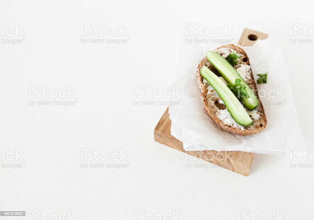 A piece of bread with butter, salt with cucumber and greens lies on a wooden board on a white background. stock photo