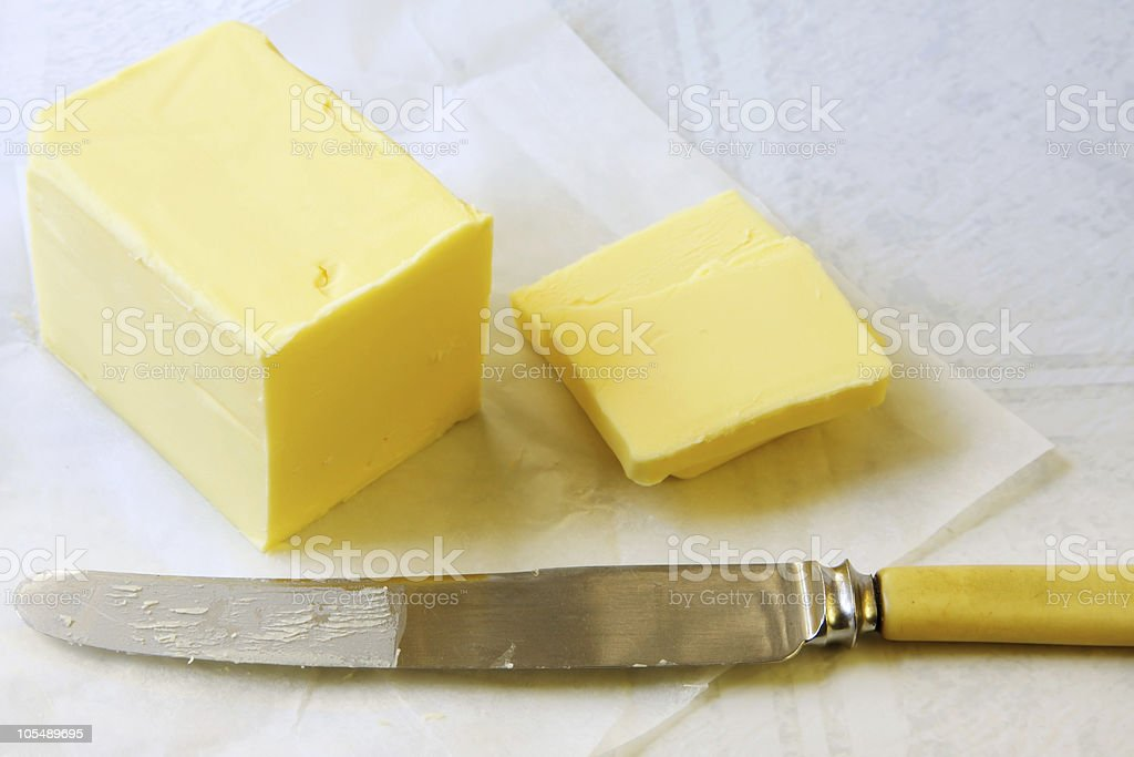 Piece of butter sliced with yellow knife royalty-free stock photo