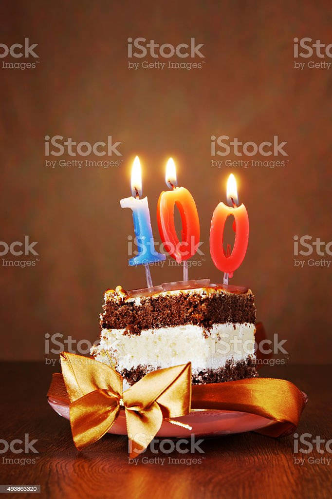 Piece of Cake with Burning Candle as Number One Hundred stock photo