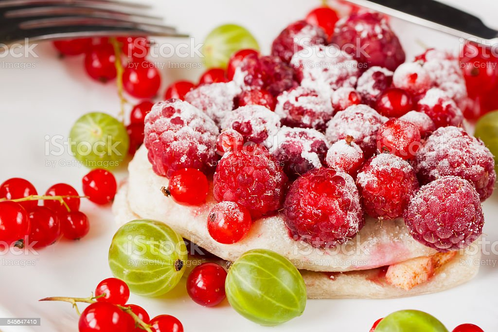Piece of cake with fresh berries on white plate stock photo