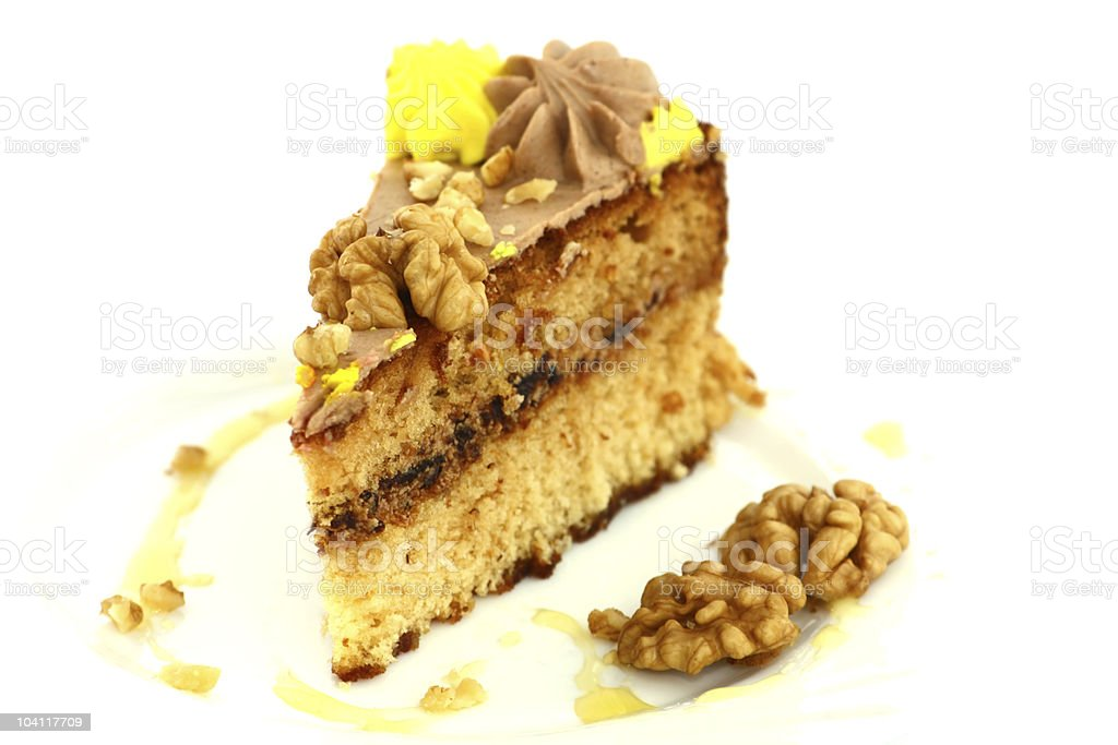 Piece of cake with walnuts isolated on white stock photo