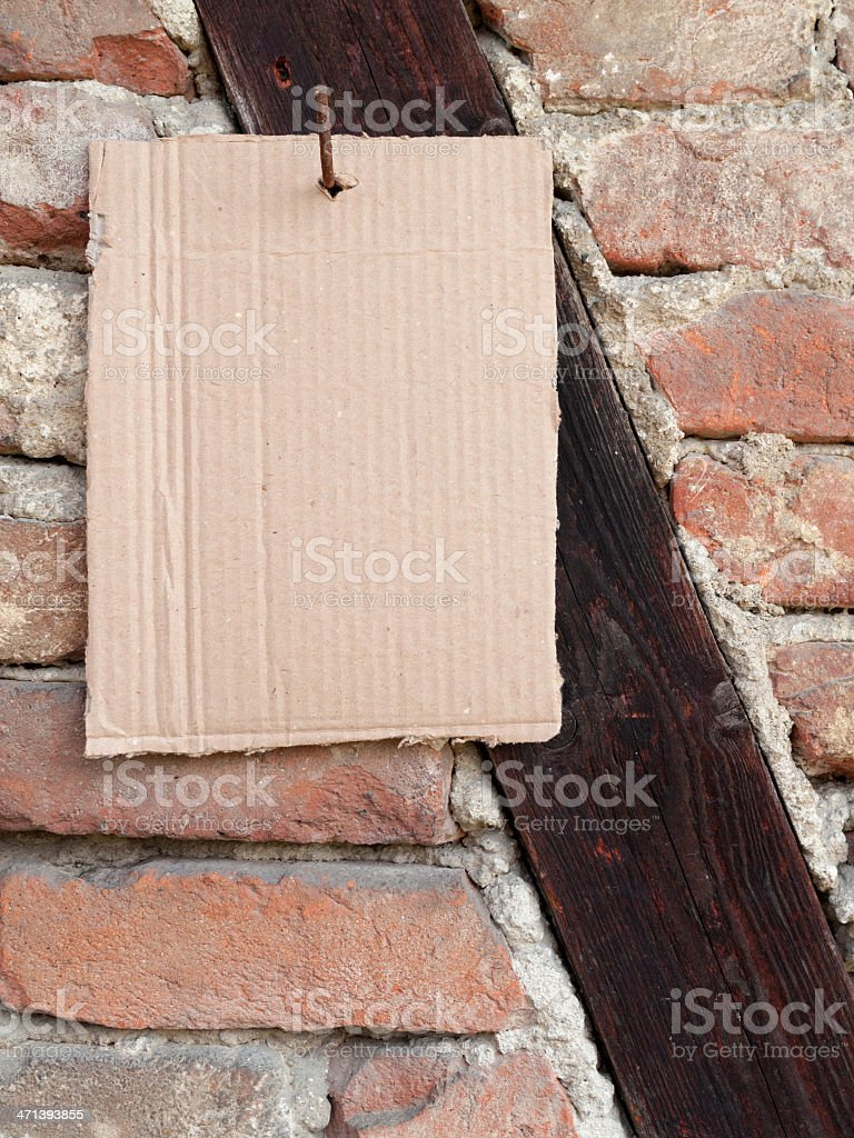 Piece of cardboard hanging from nail, an old stone wall stock photo