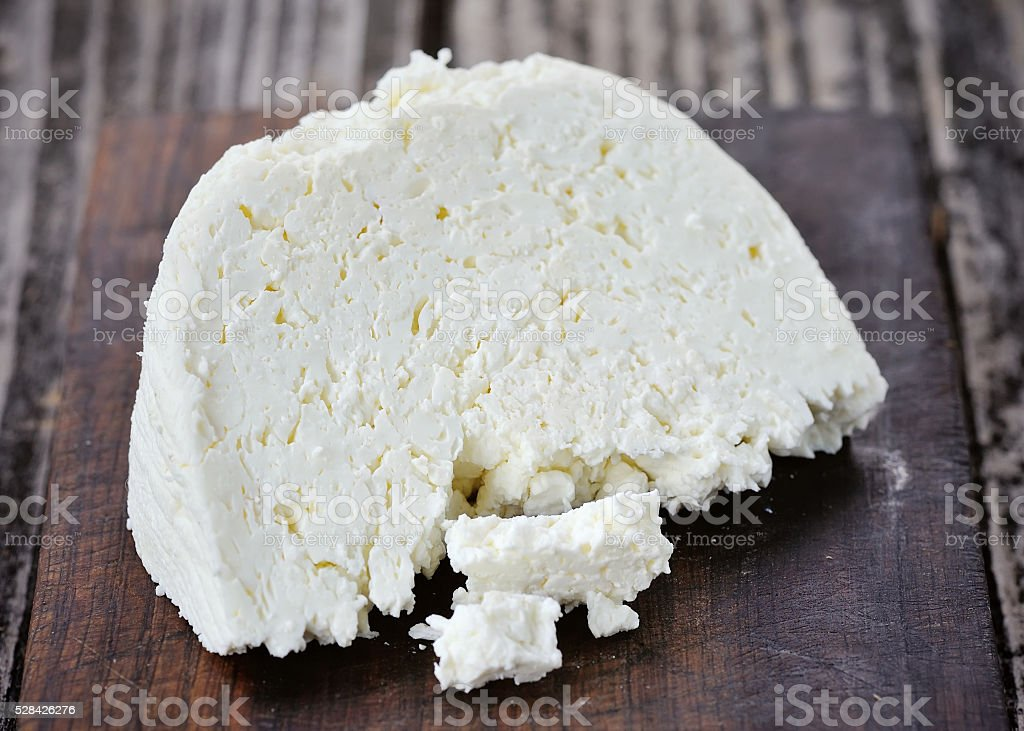 Piece of cheese on a wooden board stock photo