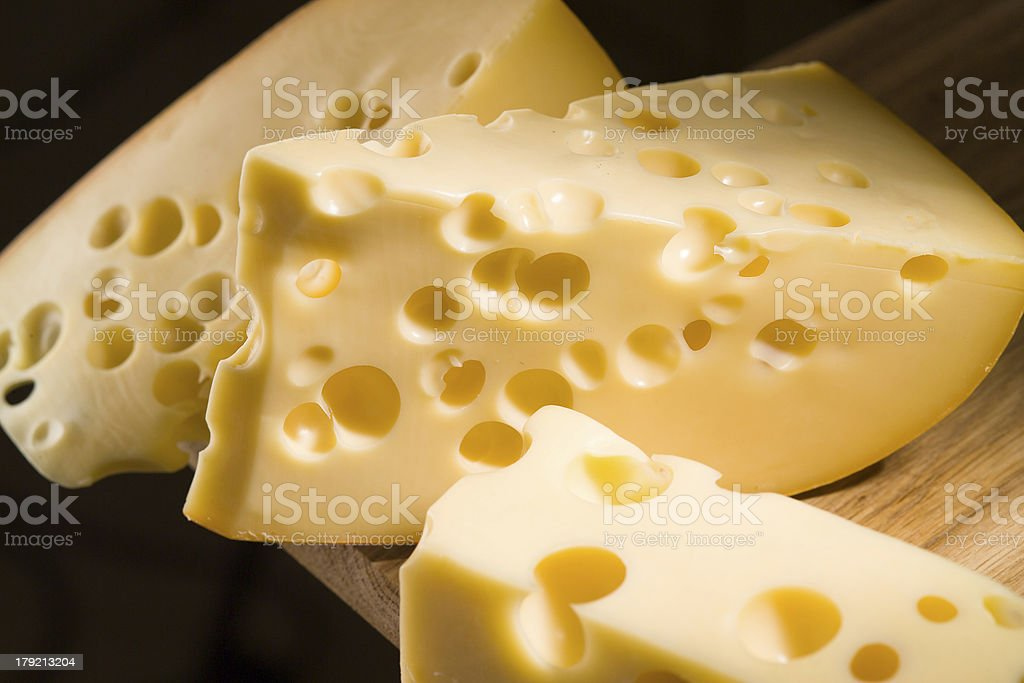 piece of cheese on wooden table royalty-free stock photo