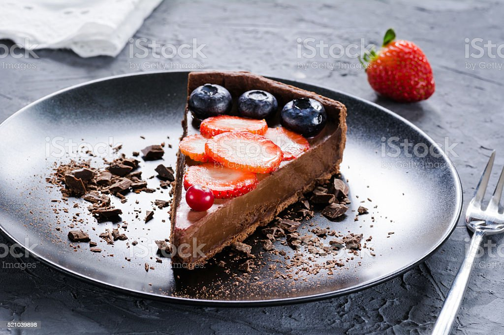 Piece of chocolate pie with fruits stock photo