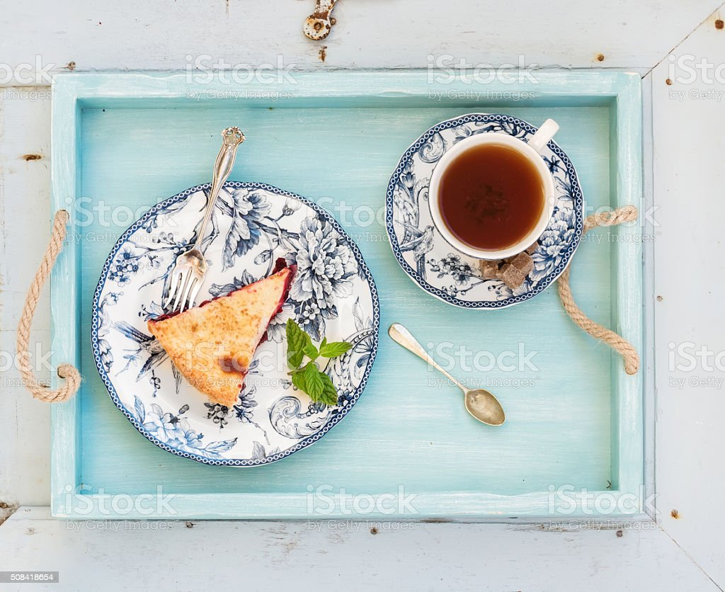 Piece of double crust plum pie and black tea in stock photo
