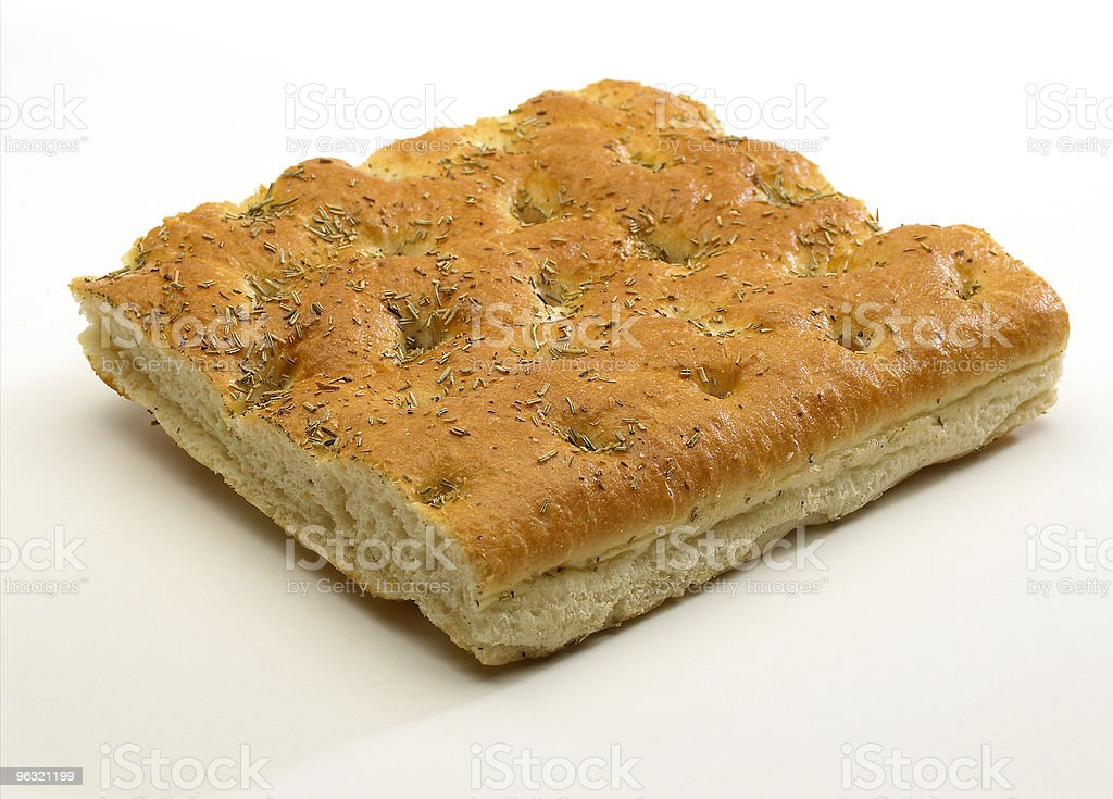 A piece of focaccia bread resting on a white surface stock photo