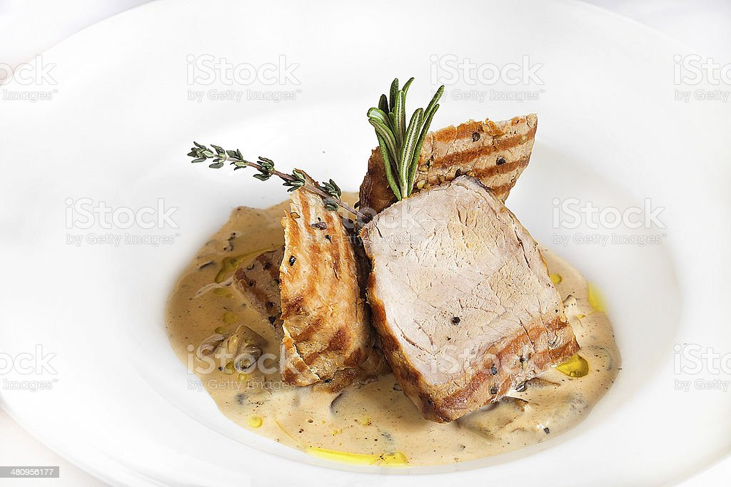 piece of fried pork with a sauce on a plate stock photo