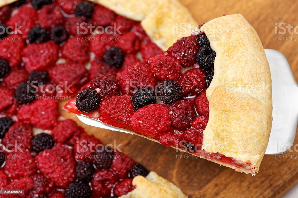Piece of galette with red and black raspberries stock photo