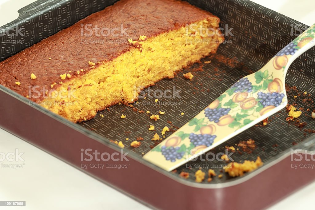 Piece of golden brown pumpkin sheet cake in baking tray stock photo