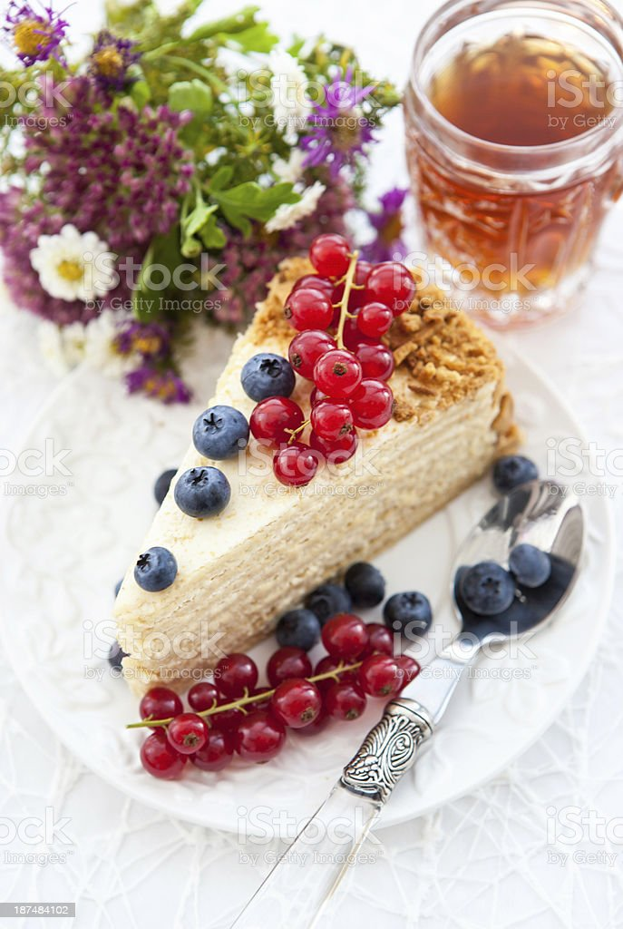 Piece of homemade honey cake decorated with fresh berries royalty-free stock photo