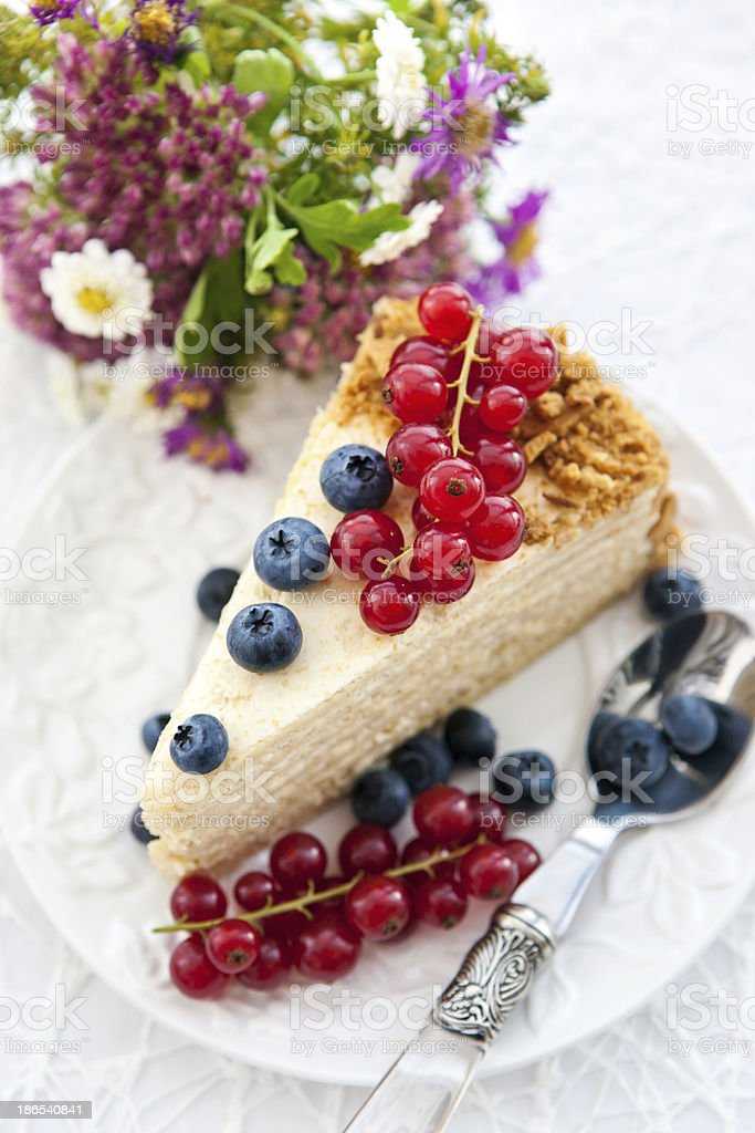 Piece of homemade honey cake with fresh berries royalty-free stock photo