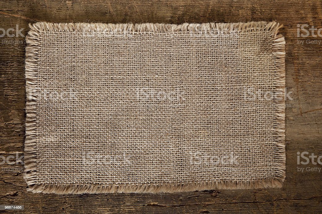 piece of jute with lacerate edges on  grunge wooden background stock photo