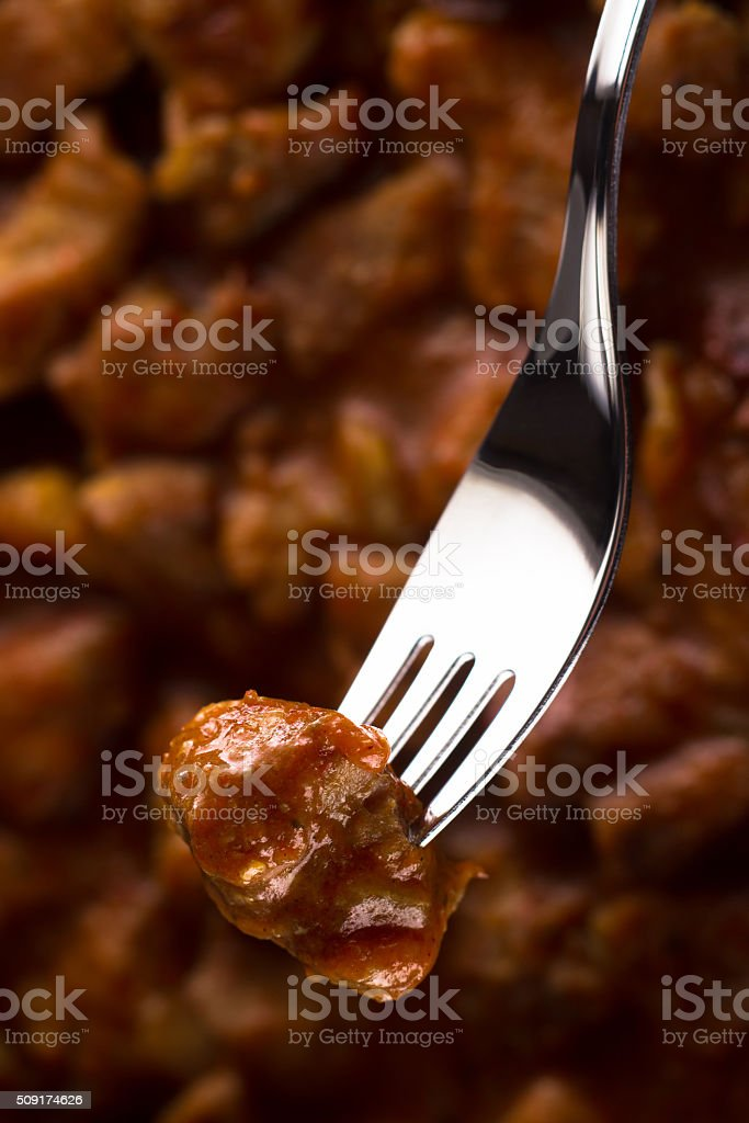 piece of meat goulash, impaled on a fork stock photo