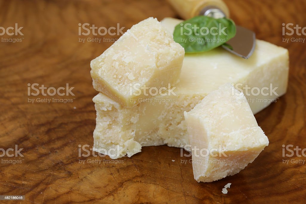 piece of natural parmesan cheese on a wooden board stock photo