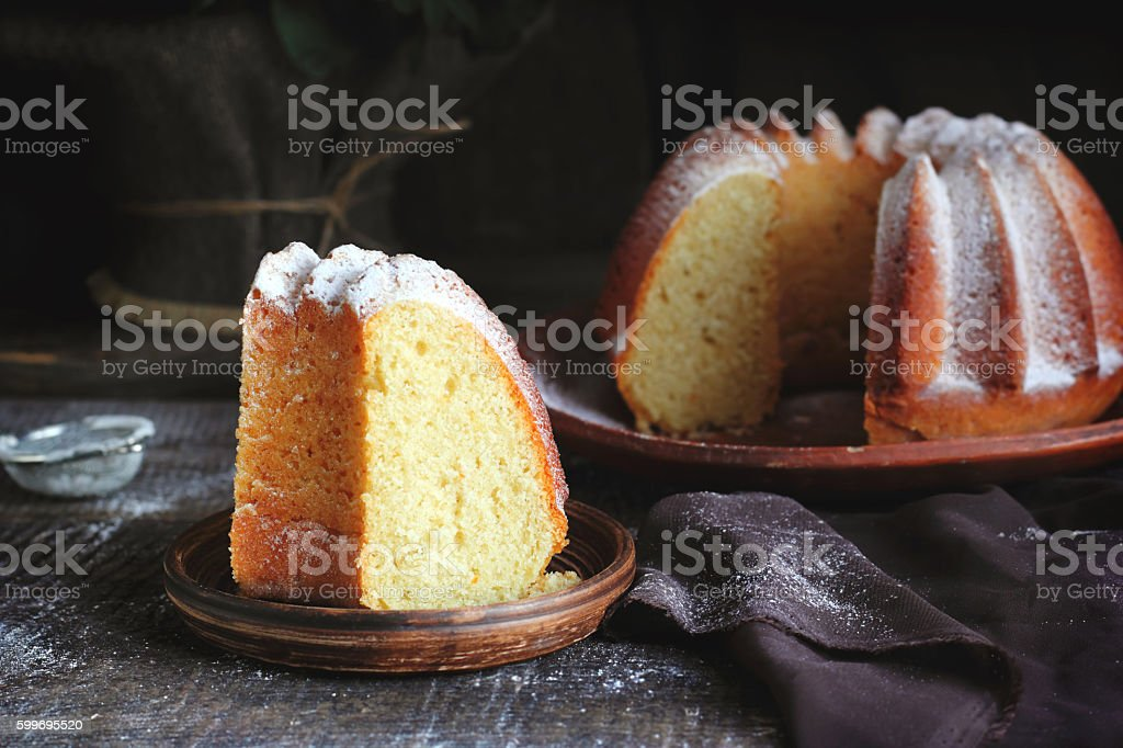 Piece of orange cake sprinkled with powdered sugar stock photo