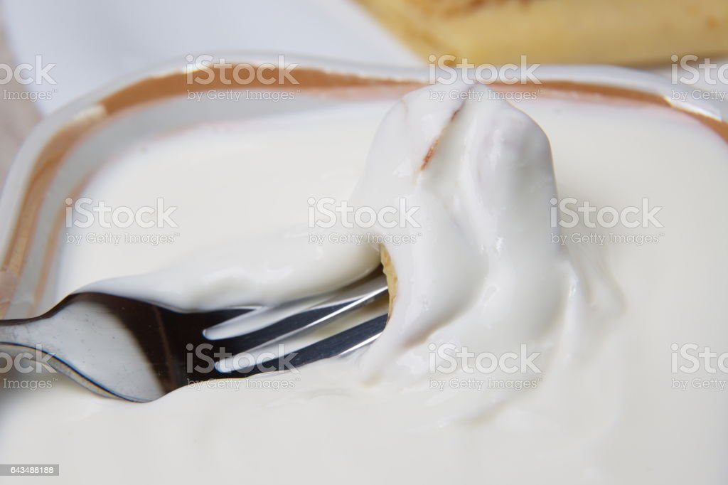 Piece of pancake in sour cream on a fork. stock photo