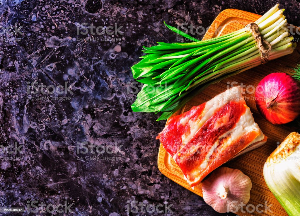 A piece of raw meat and garlic with wild garlic. stock photo