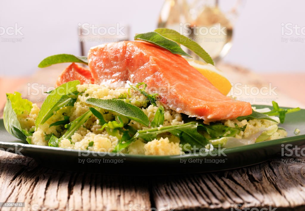 A piece of salmon lying on a bed of couscous and greens stock photo