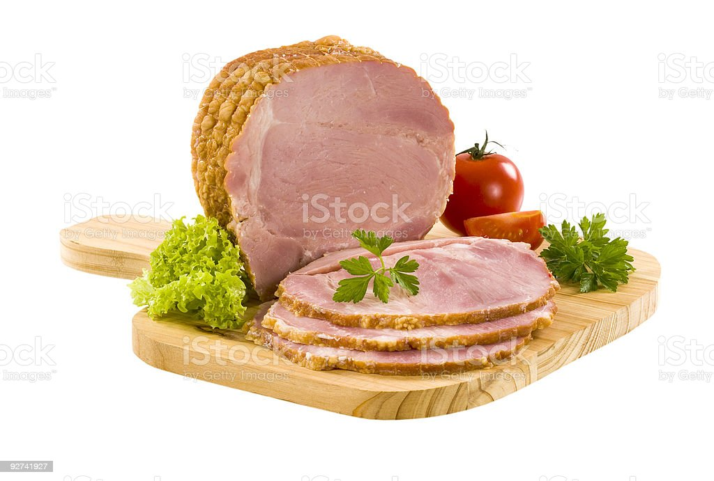 A piece of sliced smoked ham on a chopping board stock photo