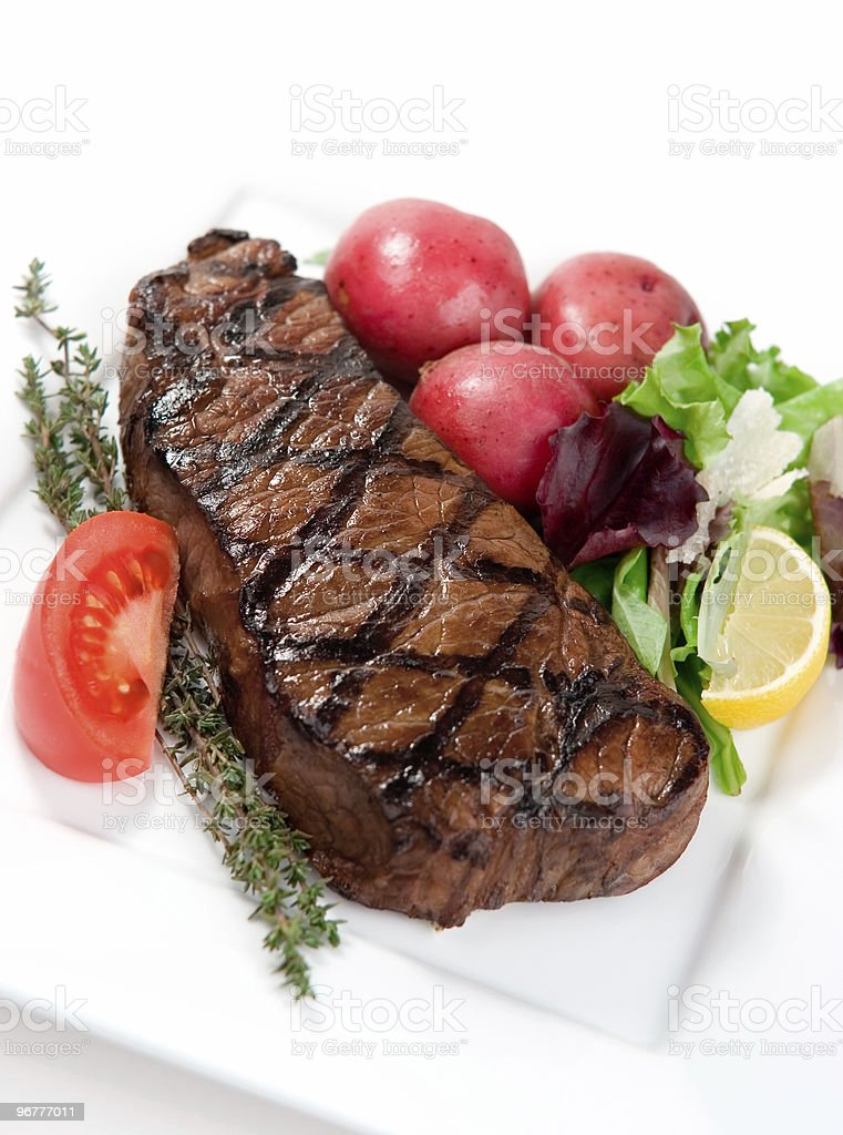 A piece of steak surrounded by vegetables stock photo
