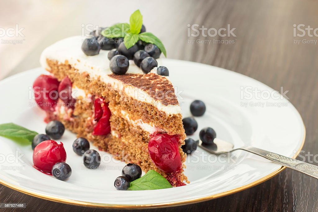 Piece of sweet cake with cherry, blueberry and mint stock photo