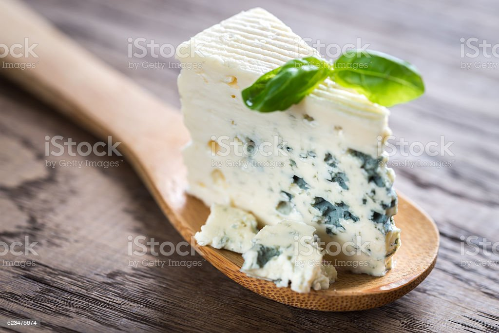 Piece of the blue cheese on the wooden spoon stock photo