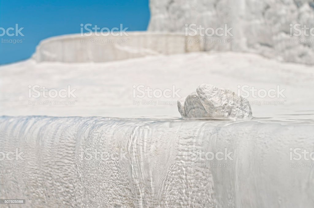 piece of travertine on travertine terrace edge against blue sky stock photo