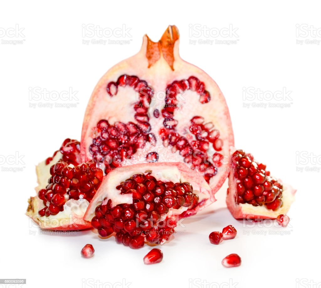Pieces and half a pomegranate on a white background stock photo