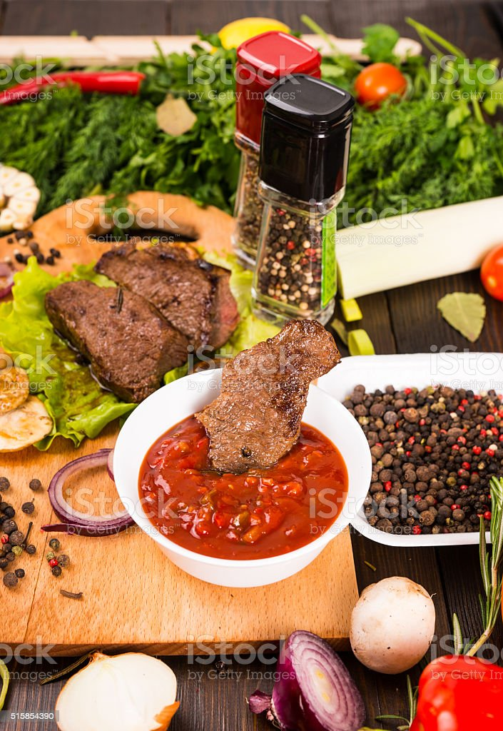 Pieces of Beef with Salsa Dip and Fresh Herbs stock photo