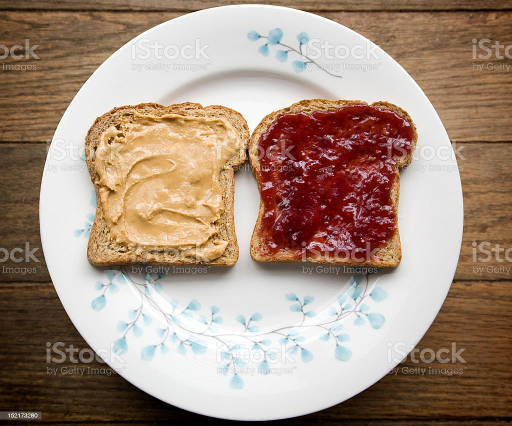 2 pieces of bread, one with peanut butter other with jelly royalty-free stock photo