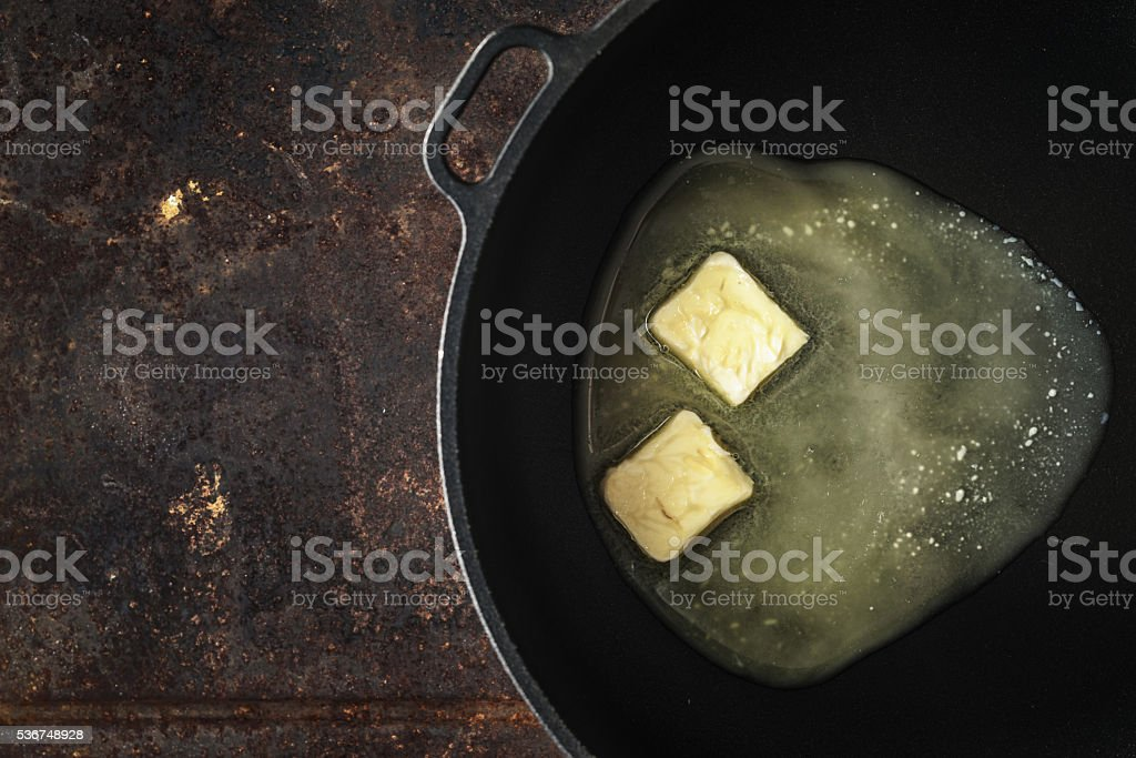 Pieces of butter in the hot pan top view stock photo