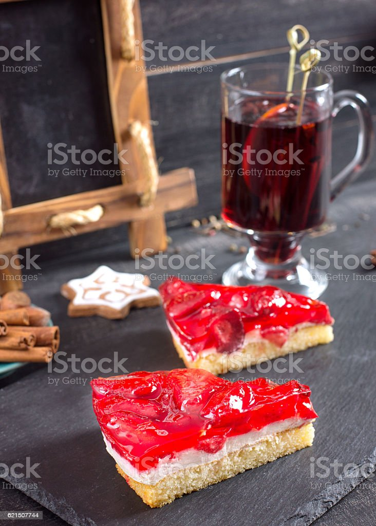 Pieces of cake with a strawberry filling and Mulled wine. stock photo