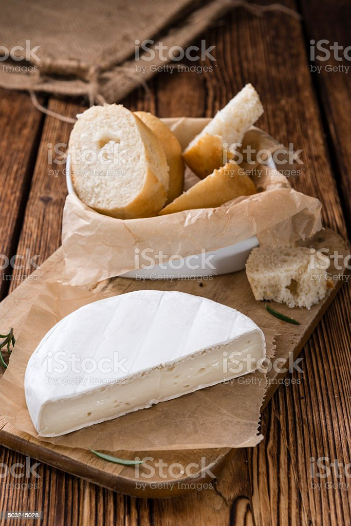 Pieces of Camembert on wooden background stock photo