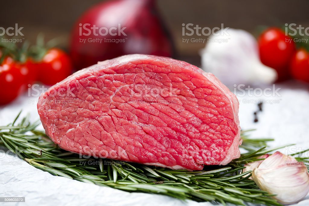 pieces of fresh meat, beef slab, decorated with vegetables. stock photo