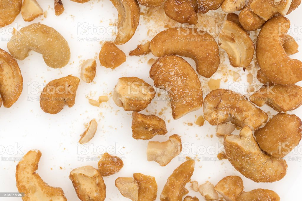 Pieces of honey roasted cashews on a white plate stock photo