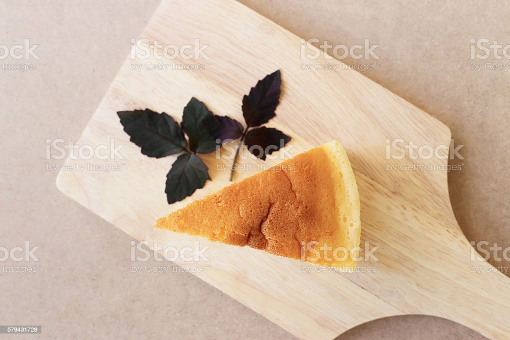 Pieces of Japanese style Cheesecake, top view on wooden plate. stock photo