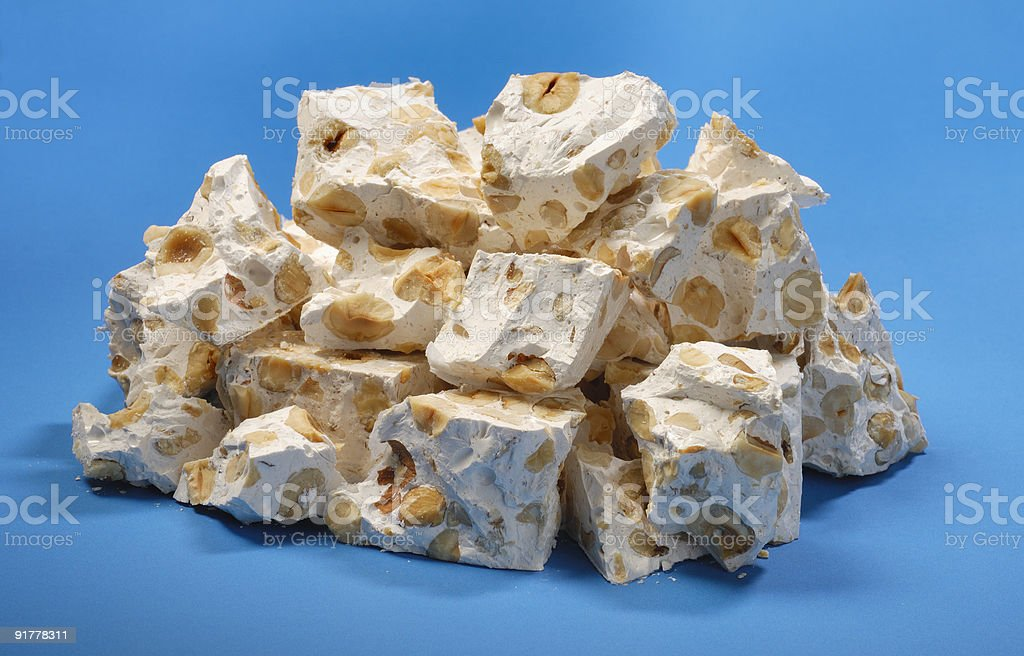 Pieces of nougat with hazelnuts on blue background stock photo