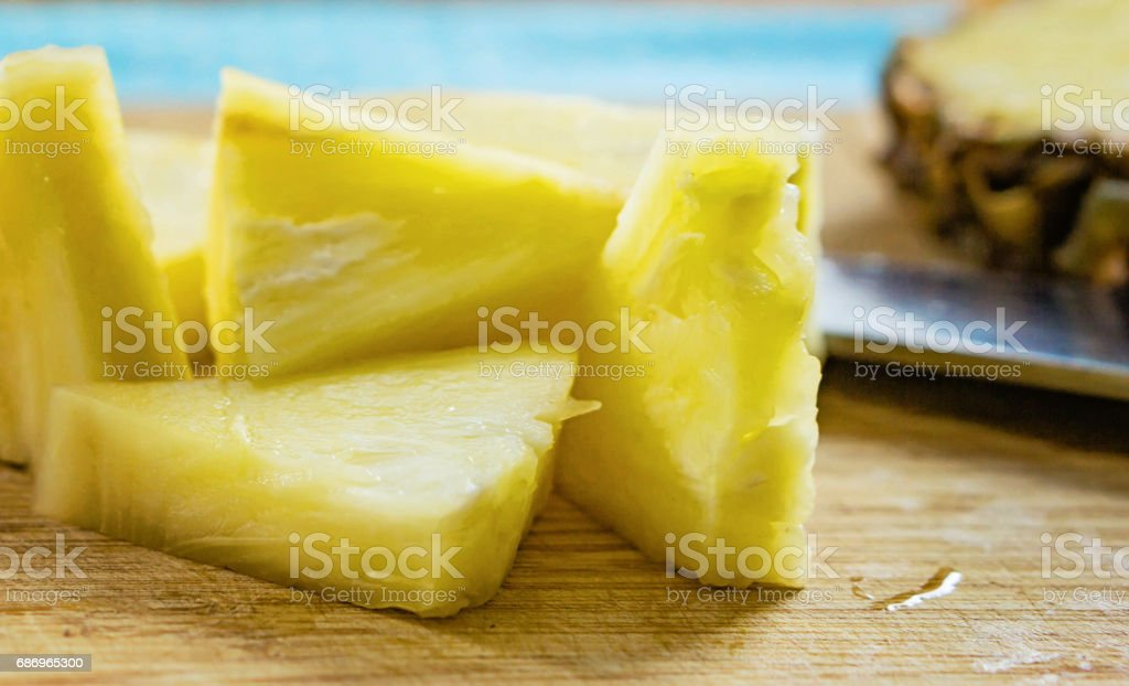 Pieces of pineapple an a wooden kitchen board with a knife and a piece of pineapple on the background by the sea stock photo