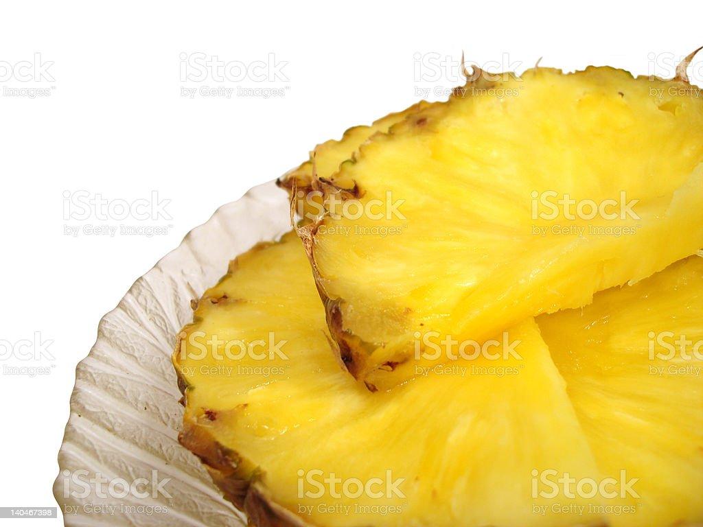 Peças de ananás em uma placa sobre fundo branco foto de stock royalty-free