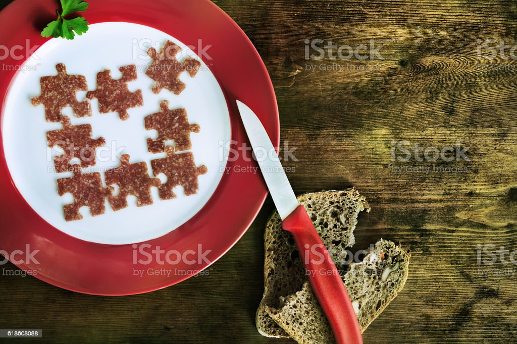 Pieces of sausage in form of puzzle stock photo