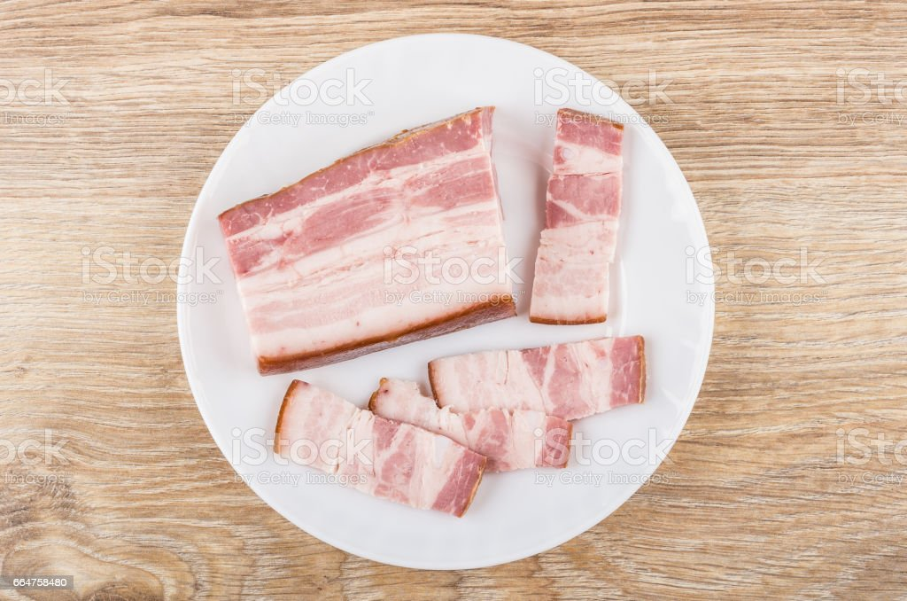 Pieces of smoked bacon in plate on wooden table stock photo