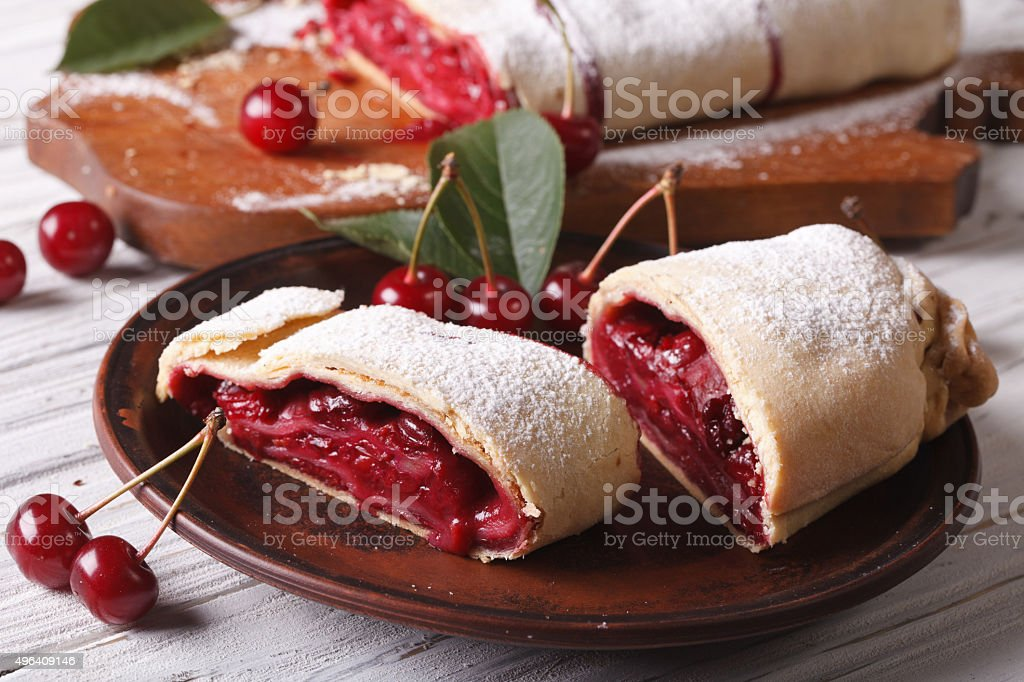 Pieces of strudel with cherry close-up on a plate. horizontal stock photo